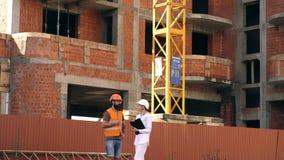 De bouwers in beschermende helmen communiceren op de bouwwerf De vrouwelijke ingenieur communiceert met de ontwikkelaar stock footage