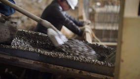 De bouwers bewegen met schoppen een cementmortier in het materiaal van de hellingsbouw op bouwgebied stock video