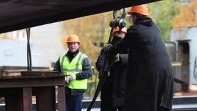 De bouwers in een helm, en trekt de kabel stock footage