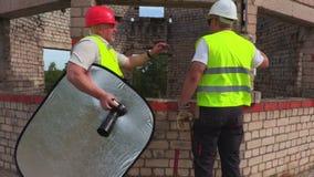 De bouwers gaan foto's op bouwwerf nemen stock video
