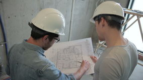 De bouwers maken reparaties in flat in nieuw huis, controleren parameters volgens het document van de tekeningsholding met blauwd stock videobeelden