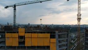De bouwers nemen cement in aanbouw van een kraan op het dak van een wolkenkrabber Uit het plakken van anker en geel stock videobeelden