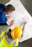 De bouwers onderzoeken blauwdrukken Stock Fotografie