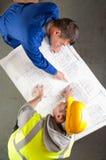 De bouwers spreken over blauwdruk op bank Royalty-vrije Stock Fotografie