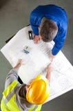 De bouwers spreken over blauwdruk op bank Royalty-vrije Stock Foto's