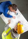 De bouwers spreken over blauwdrukken Royalty-vrije Stock Foto