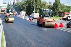 De bouwers zet asfalt Stock Afbeeldingen