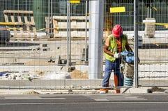 De bouwersarbeider bij bouwwerf maakt stoep dichtbij de nieuwe bureaubouw Vilnius, Litouwen - Juni 29, 2016 Stock Afbeelding