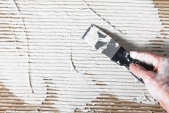 De bouwershand met spatel spreidde wit pleister uit Stock Foto