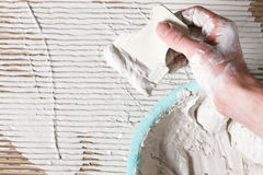 De bouwershand met spatel, wit vlak pleister, legt Stock Afbeeldingen