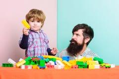 de bouwhuis met aannemer Gelukkige Familie De zomer dreems vader en zoonsspelspel Kindontwikkeling Weinig jongen met stock fotografie