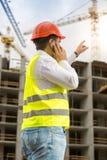 De bouwingenieur die met vinger op de bouw richten bedriegt onder Royalty-vrije Stock Afbeeldingen