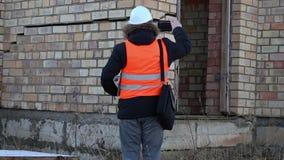 De bouwinspecteur filmde bij de barsten in de de bouwmuur stock footage