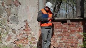 De bouwinspecteur neemt beelden op tabletpc dichtbij venster stock videobeelden