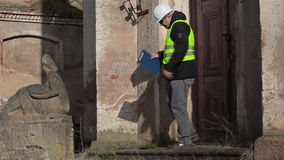 De bouwinspecteur probeert open de deur dan spreekt op slimme telefoon stock videobeelden