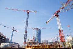 De bouwkranen bouwen huizen in een grote stad nacht De Spits van Warshau Warschau Stad polen stock foto's