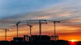 De bouwkranen die bij zonsondergang, arbeiders werken namen in bouw, tijdtijdspanne in dienst royalty-vrije stock foto's
