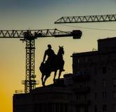De bouwkranen en een oorlogs herdenkingsgestalte kunnen over worden gezien Stock Afbeeldingen