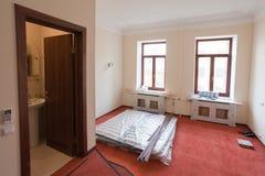 De bouwmaterialen, het meubilair en de telefoon zijn in aanbouw op de vloer van flat in het hotel tijdens Stock Afbeeldingen
