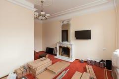 De bouwmaterialen, het meubilair, TV en de telefoon zijn op de vloer in flat met retro open haard van het hotel Stock Afbeeldingen