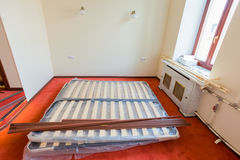 De bouwmaterialen, het meubilair, TV en de telefoon zijn op de vloer van flat in het hotel tijdens ondervernieuwing Stock Fotografie