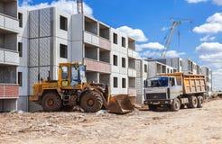De bouwtechnieken bevindt zich dichtbij een woningbouw onder c Stock Fotografie