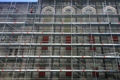 De bouwvakker assembleert steiger op een bouwterrein Stock Afbeelding
