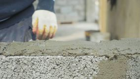 De bouwvakker bouwt bakstenen muur, close-upmening bij bouwwerf