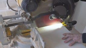 De bouwvakker die schuifsamenstelling gebruiken bewerkt zaag of cirkelzaag voor het snijden van massieve houten raad in verstek stock footage