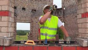 De bouwvakker drinkt thee of koffie dichtbij hulpmiddelen stock video
