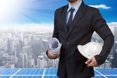 De bouwvakker en de blauwdruk van de ingenieursholding voor het werken bij zonneener stock afbeeldingen