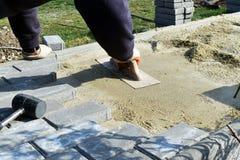 De bouwvakker legt concrete bestratingssteen voor het voetpadwerk bij de bouwwerf De straatsteenarbeider zet stock afbeeldingen