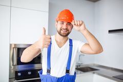 De bouwvakker, maakt helm op hoofd recht, glimlacht en toont duimengebaar royalty-vrije stock foto