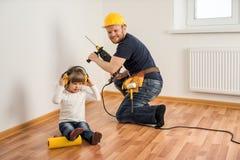 De bouwvakker met een boor en een klein kind maken reparaties stock foto