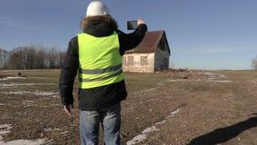 De bouwvakker neemt beelden dichtbij verlaten huis stock videobeelden