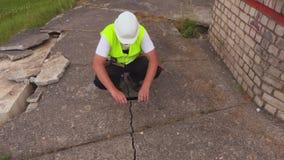 De bouwvakker neemt foto's op tablet bij de gebarsten concrete plak stock video