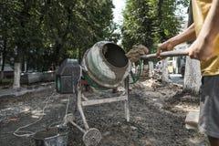 De bouwvakker voegt ingrediënten voor zich het mengen in de concrete mixer bij bouwterrein toe gebruikend schop tijdens stoep royalty-vrije stock fotografie