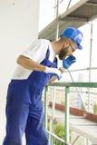 De bouwvakker in werkende uitrusting en in beschermende helm bevindt zich bij hoge hoogte op bouwwerf stock foto
