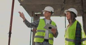 De bouwvakkerman en de architectenvrouw in een helm, bespreken het plan van bouw van huis, vertellen elkaar stock videobeelden