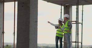 De bouwvakkerman en de architectenvrouw in een helm, bespreken het plan van bouw van huis, vertellen elkaar stock video