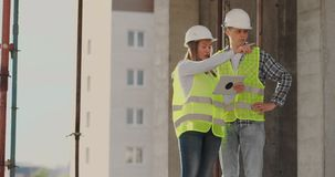 De bouwvakkerman en de architectenvrouw in een helm, bespreken het plan van bouw van huis, vertellen elkaar stock footage