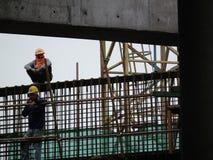 De bouwvakkers installeren staalstaven in het gewapend beton post concrete staal van de spanningsplaats stock foto