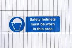 De bouwvakkers van veiligheidshelmen moeten versleten teken zijn bij bouwwerf stock fotografie