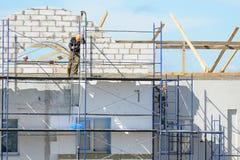 De bouwvakkers voeren het werk bij het pleisteren en de isolatiebouw uit Royalty-vrije Stock Fotografie