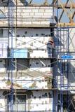 De bouwvakkers voeren het werk bij het pleisteren en de isolatiebouw uit Stock Foto