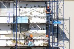 De bouwvakkers voeren het werk bij het pleisteren en de isolatiebouw uit Stock Fotografie