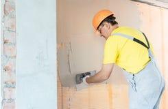De bouwvakkerstopverf een muur stock foto