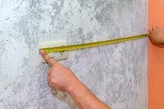 De bouwwerkzaamheid, een arbeider meet de muur met een de bouwmeetlint stock afbeelding