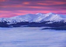 De bovenkant van de bergen onder een overzees van mist Stock Afbeelding