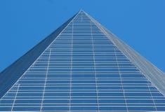 De bovenkant van de glaspiramide van een wolkenkrabber tegen blauwe hemelachtergrond Royalty-vrije Stock Foto